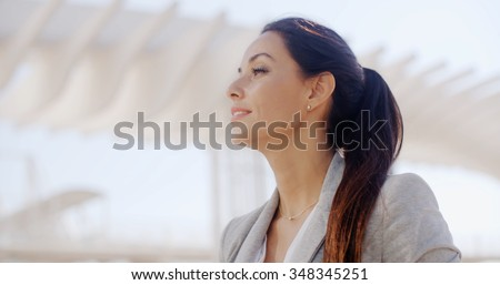 Low angle head and shoulders portrait of a gorgeous sophisticated woman with long brown hair in a ponytail in a high key outdoor  urban  environment  with copyspace. - stock photo