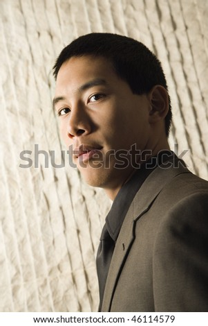 Low angle head-and-shoulders portrait of Asian young adult businessman. Vertical format. - stock photo