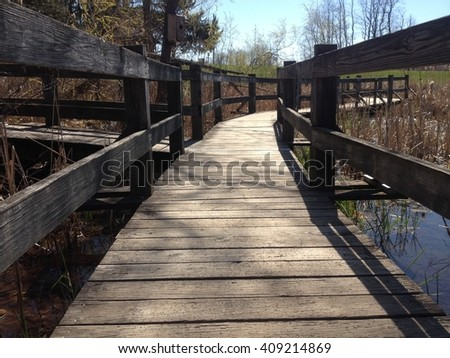 Low angle of a sidewalk bridge leading over a pond