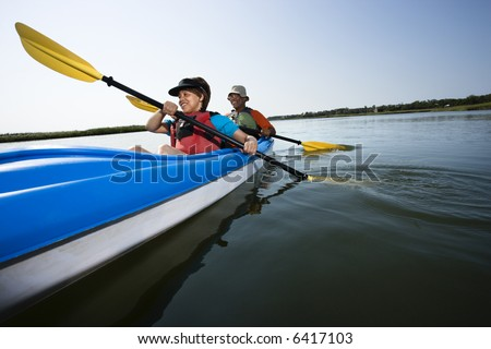 Low angle of African American middle-aged man and woman paddling kayak. - stock photo
