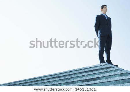 Low angle of confident businessman standing on marble staircase against clear sky - stock photo