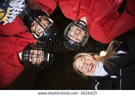 Low angle of female hockey players in huddle with coach smiling.