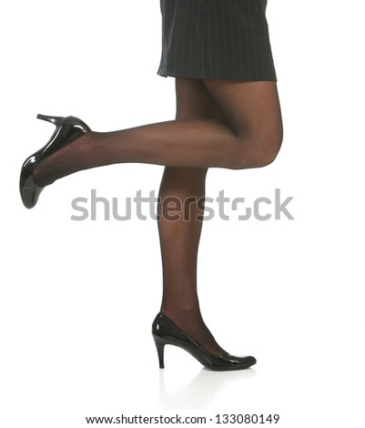 Low angle of legs and heels of business woman isolated against white background - stock photo