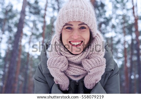 Low angle of woman face with blue eyes and perfect make-up isolated in the wintry forest. A walk in the wintry forest