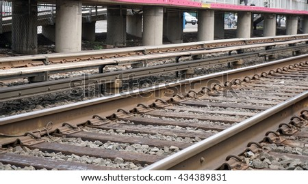 Low angle photo of the third rail. Electrified high voltage power source for electric train engines to run and travel busy commuters between work and home - stock photo