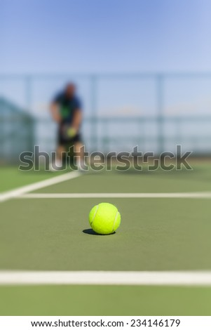 Low angle photograph in a hard court with a tennis ball next to camera. Unrecognizable tennis player serving at the background.