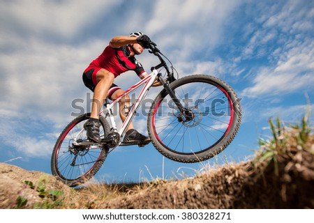 Low angle portrait against blue sky of mountain biker going downhill. Cyclist in red sport equipment and helmet.