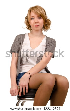 Low angle portrait of a young pretty woman with curly blonde hair sitting on a stool in shorts isolated on white - stock photo