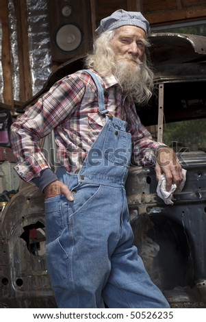 Low angle portrait of an elderly man with a beard and coveralls, standing in a garage in front of a vehicle he is restoring. - stock photo