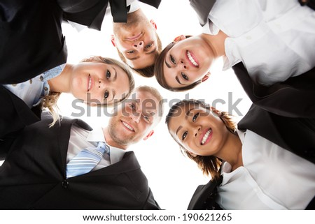 Low angle portrait of business people forming huddle against white background