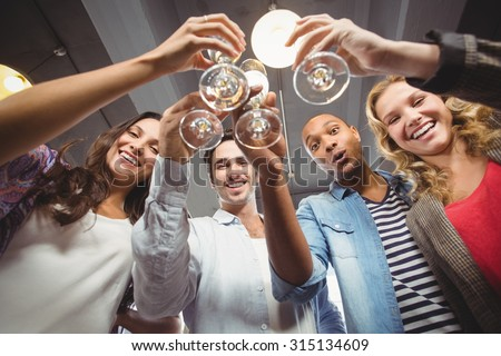 Low angle portrait of happy colleagues toasting with champagne in creative office - stock photo