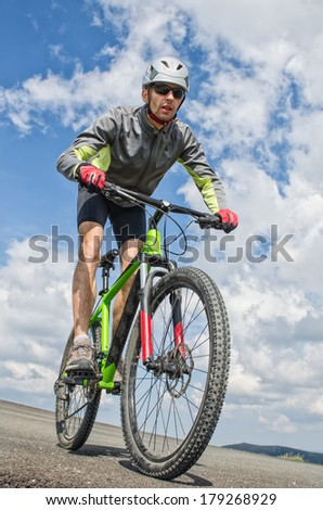 low angle portrait of mountain biker going downhill - stock photo