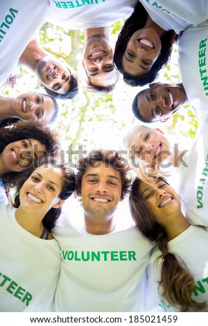 Low angle portrait of multiethnic environmentalists forming huddle - stock photo