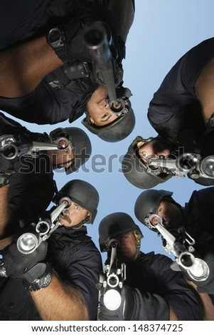 Low angle portrait of policemen aiming with guns against sky - stock photo
