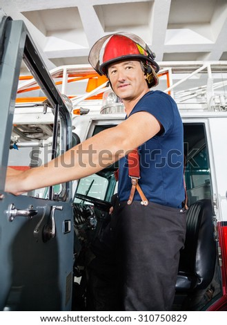 Low angle portrait of smiling fireman standing on truck at fire station