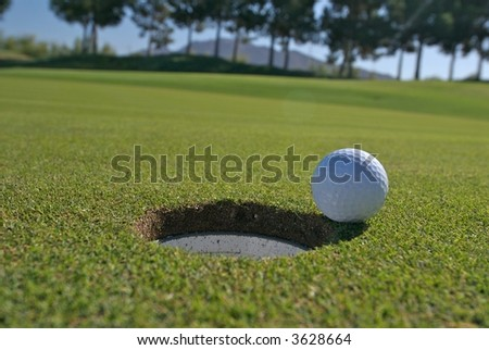 Low angle shot of a golf ball next to the hole - stock photo