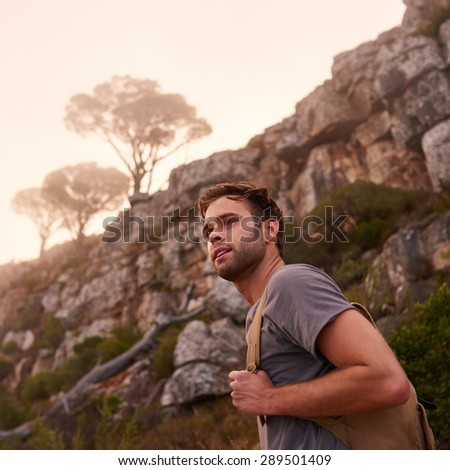 Low angle shot of a handsome guy on a nature trail with a view of the misty mountain top behind him - stock photo