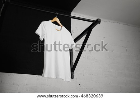 Low angle shot of a plain white cotton shortsleeve t-short on a hanger hanging on pullup bar in a room with brick walls painted in white.
