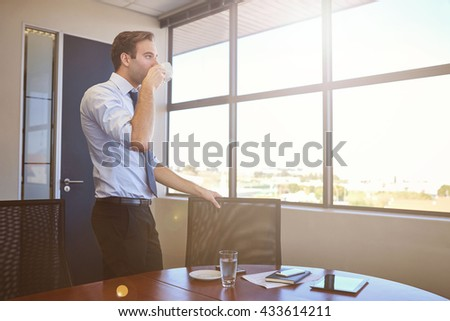 Low angle shot of a young businessman standing in a modern meeting room with large windows, looking out at the view while sipping a cup of coffee, with gentle sunflare - stock photo