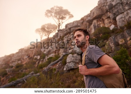 Low angle shot of a young male hiker on a nature trail with the misty mountain top and trees behind him - stock photo