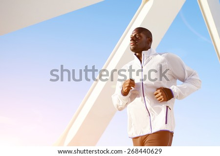 Low angle shot of an attractive dark skinned sporty man on a morning run outdoors over blue sky background - stock photo