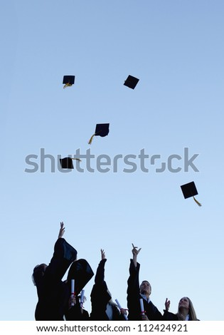 Low angle-shot of five grad students throwing their hats high in the sky - stock photo
