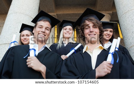 Low angle-shot of graduate posing in front of their university - stock photo