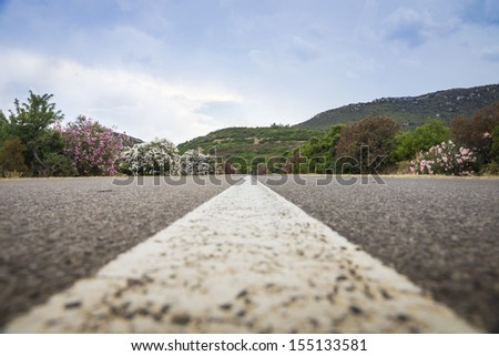 low angle shot of road line on scenic road - shallow depth of field - stock photo