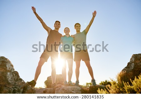 Low angle shot of three athletic friends standing on a rocky mountain and posing triumphantly - stock photo