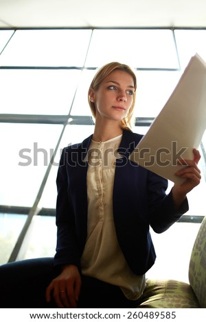 Low angle shot with young blond hair business woman examining paperwork in bight light office interior sitting next to the window, attractive business woman read some documents before meeting - stock photo