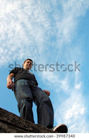 Low angle side view of young man stays on the stone edge, blue sky and cloudscape background