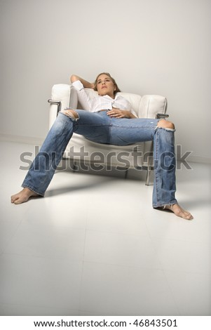 Low angle tilted view of a young woman relaxing in an armchair. Vertical shot. - stock photo