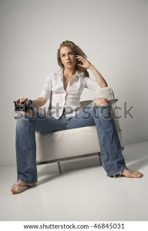 Low angle tilted view of a young woman seated in a white armchair and holding a camera. Vertical shot. - stock photo