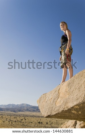 Low angle view a female climber standing on rock and looking at desert - stock photo