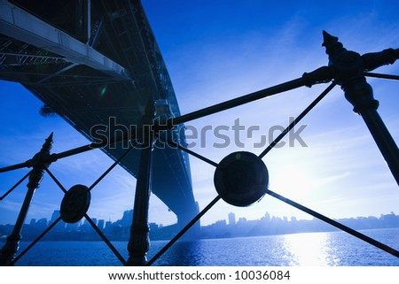 Low angle view at dusk from under Sydney Harbour Bridge in Australia with view of skyline and harbor. - stock photo