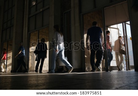 Low angle view at floor level of shoppers entering and leaving a store in a commercial shopping mall or underground entrance - stock photo
