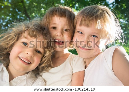 Low angle view closeup portrait of happy friends in spring park. Three funny kids looking in camera