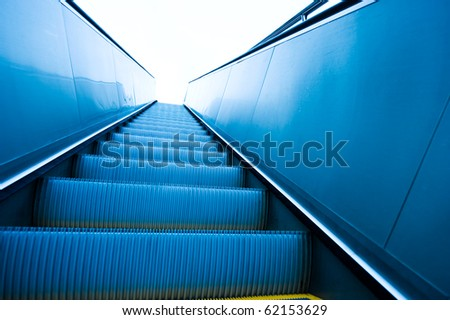 Low angle view looking to top of modern escalator with blue tone. - stock photo