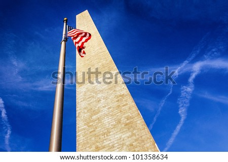 Low angle view looking to top of Washington monument with American flag, blue sky and cloudscape background.