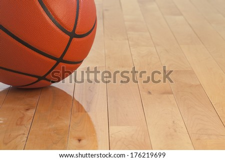 Low angle view of a basketball on a wooden gymnasium floor - stock photo