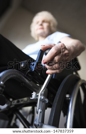 Low angle view of a blurred senior woman operating wheelchair - stock photo