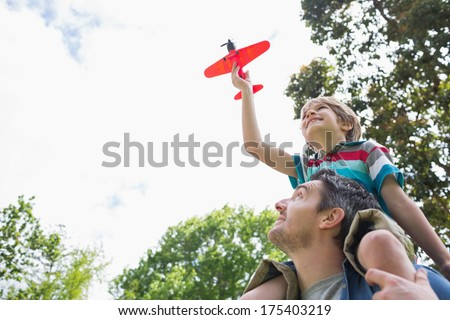 Low angle view of a boy with toy aeroplane sitting on father's shoulders at the park - stock photo