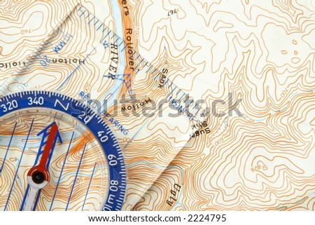 Low angle view of a compass on a topographic map pointing to a river - stock photo