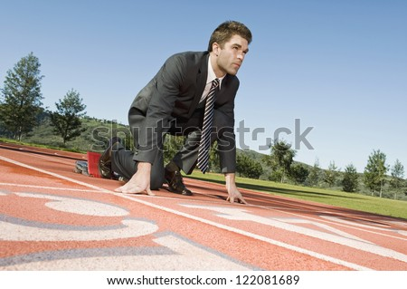 Low angle view of a confident businessman at starting position of a race track - stock photo