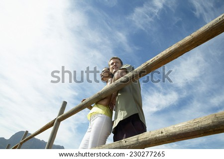 Low angle view of a couple leaning on a log fence against blue sky
