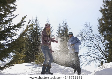 Low angle view of a couple playing in snow on hill - stock photo