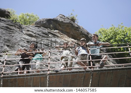 Low angle view of a couple with three children looking down from bridge against rocks - stock photo