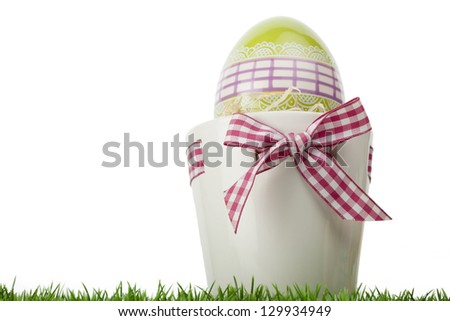 Low angle view of a decorative Easter Egg gift with a green ornamental l egg inside a flower pot tied with a fresh red and white checked ribbon and bow on grass isolated on white with copy space - stock photo