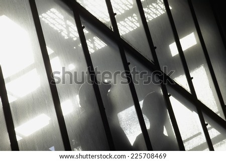 Low angle view of a factory worker silhouetted in window