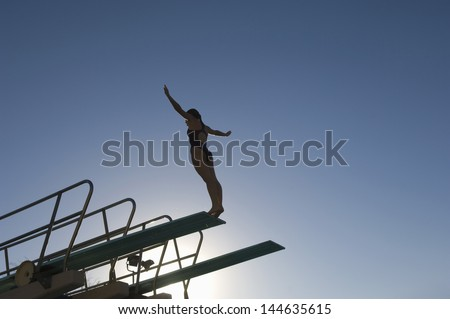 Low angle view of a female diver with arms out about to dive against the blue sky - stock photo
